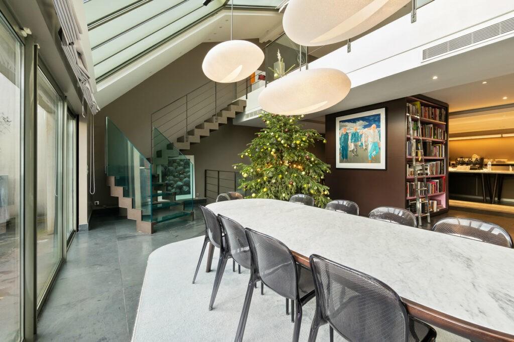 Une immense verrière surplombe, une très grande table a manger en marbre. La pièce donne sur un escalier ouvert. la décoration est très minimaliste.
