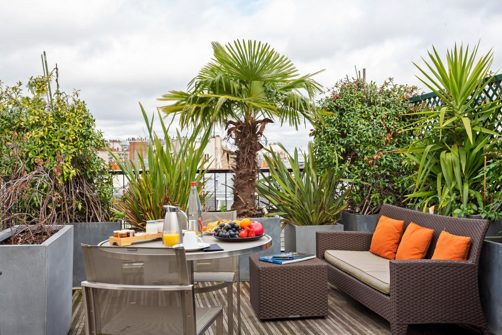 Petite terrasse rectangulaire avec des palmiers, et autre pots de fleurs en béton. Un salon de jardin y est installé, ainsi qu'une table avec deux chaises et un petit déjeuner dressé (fruits et jus)