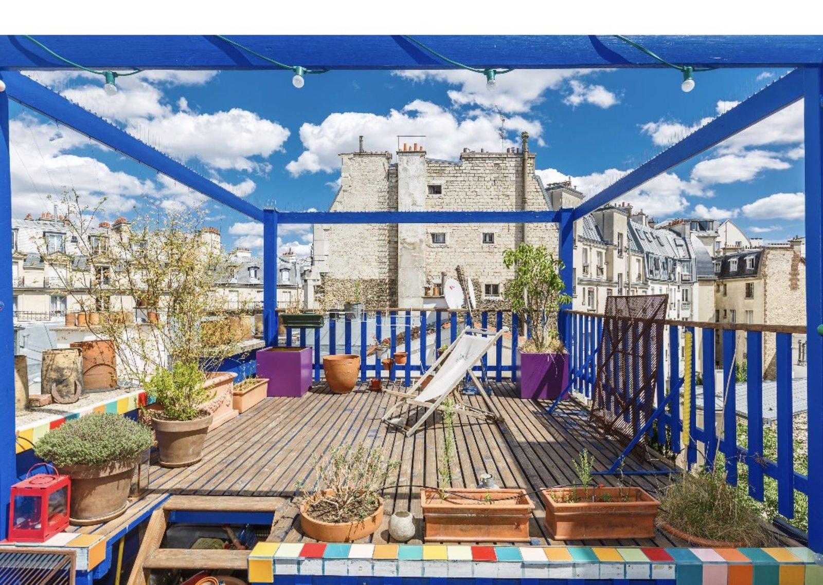 Terrasse très coloré avec une armature et une barrière bleu majorelle. Du carrelage peint de différente couleur se place autour de la terrasse. Accompagné de quelque jardinière en terre. Il y a une vue dégagé sur divers immeubles et toits de Paris.