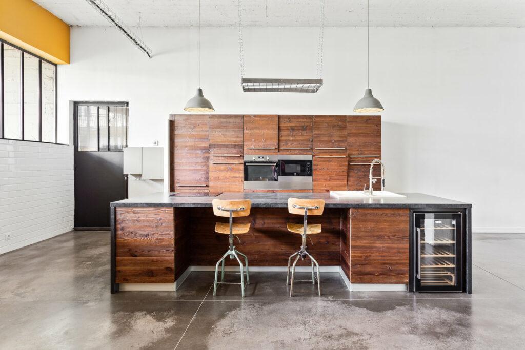 Une cuisine brute et minimaliste est décorée au style industriel. Cette cuisine a du caractère. Pour un repas entre collaborateur c'est l'endroit rêvé.