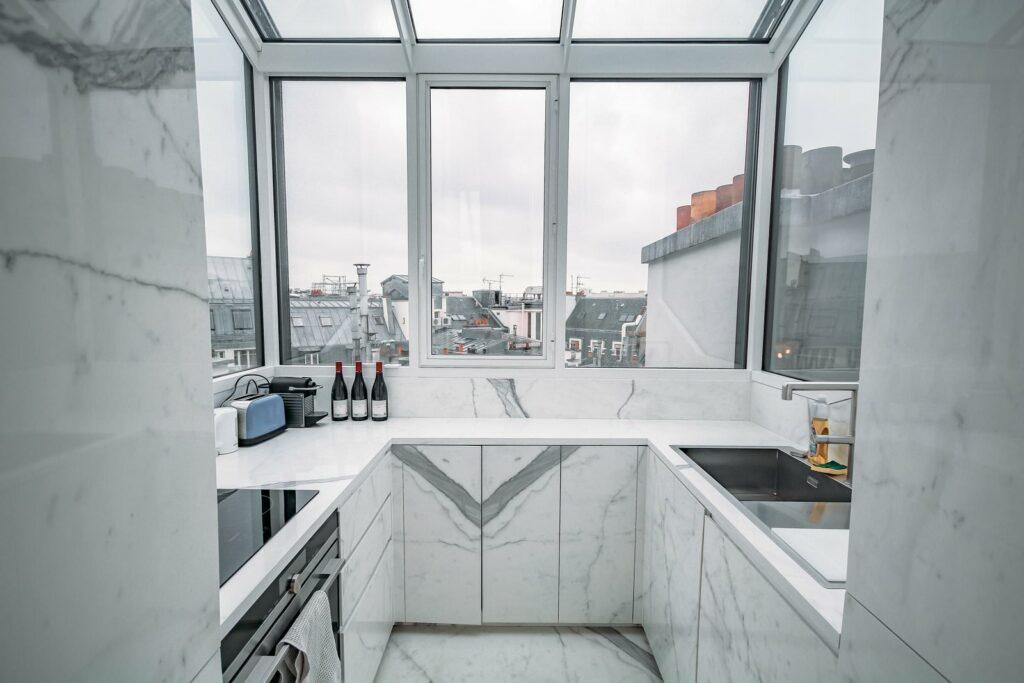 Une cuisine faite de marbre blanc, face à une sublime vue sur les toits de Paris. Cette cuisine est même  trop bien pour un magazine.