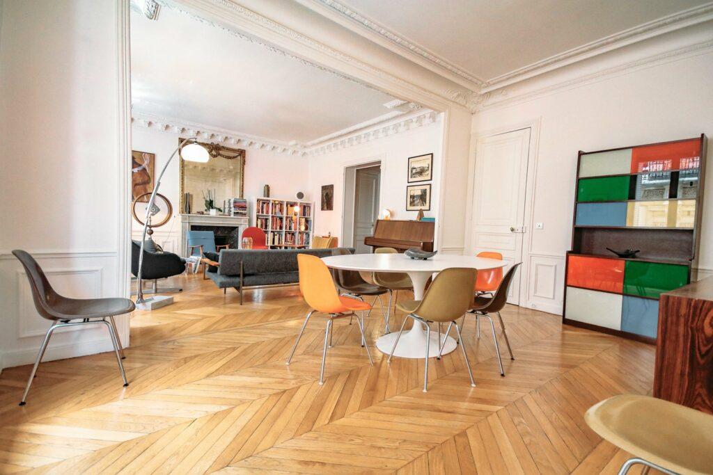 Appartement très spacieux avec une partie salle à manger et salon séparé de d'une ouverture murale. La table à manger est ronde disposée avec des chaises vintage orange. Dans l'autre partie de la piéce on distingue le salon avec un canapé et quelques assises face à la cheminée et un grand miroir qui surplombe le tout.