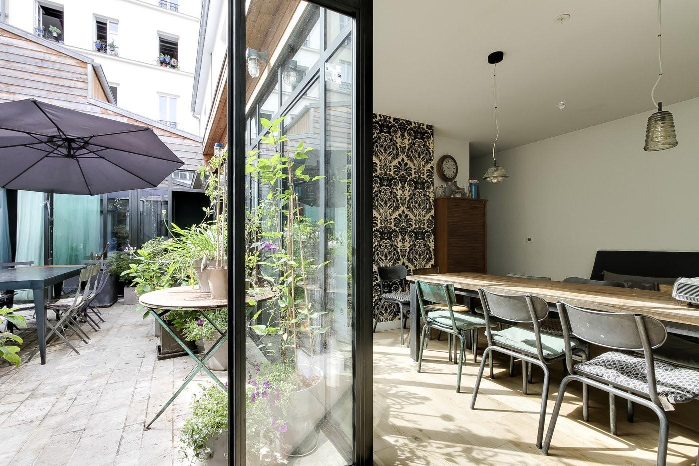 Vue double sur l'intérieur d'un loft moderne et de sa terrasse arborée