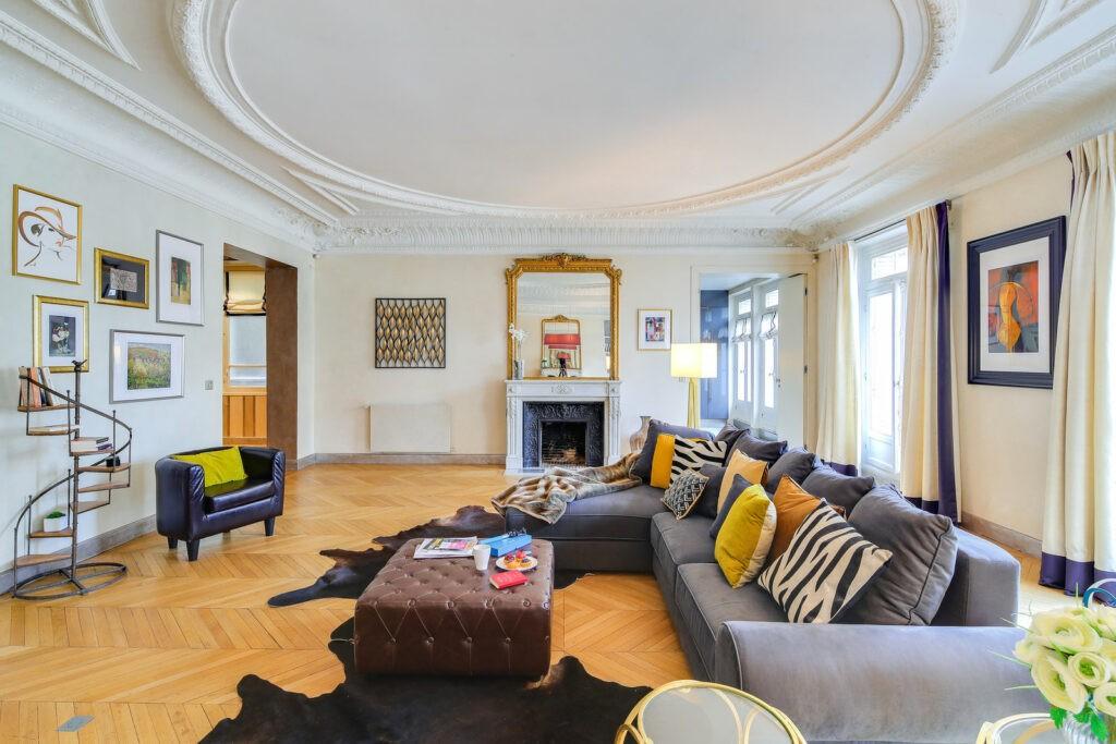 salon cosy avec grand canapé dans un appartement haussmannien avec moulures