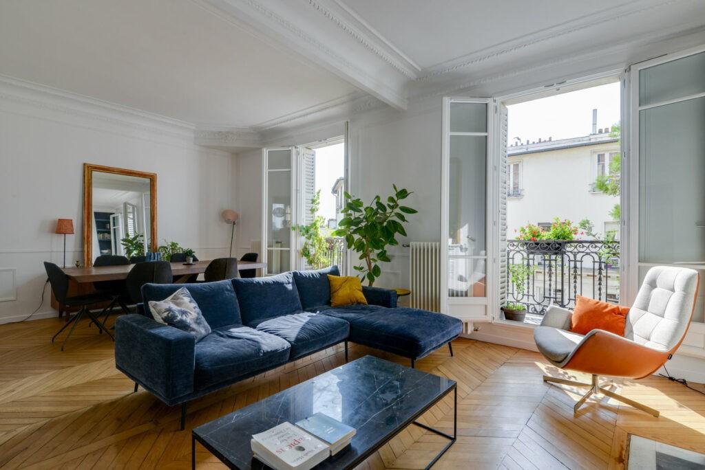 Appartement Haussmanien, configuré de façon à ce que la salle à manger et le salon soient dans la même pièce. Un canapé d'angle bleu est situé au milieu de la pièce, dos à la table a manger. Un table  basse et un fauteuil sont disposés