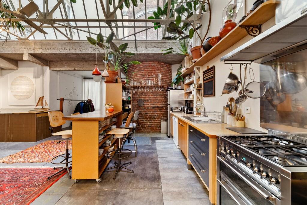 Une verrière végétales surplombe les fourneaux au style industriel. Tout en longueur et ouverte sur un immense espace.