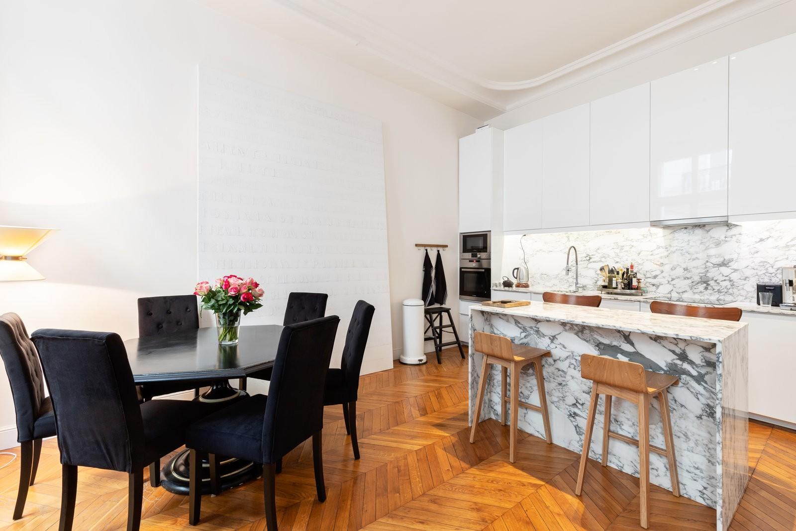 Cuisine ouverte en marbre et mobilier blanc. Des chaises sont disposées autour du bar/plan de travail central. Ouverte sur un espace où se trouve une table ronde noir et ses 6 chaises noir également.