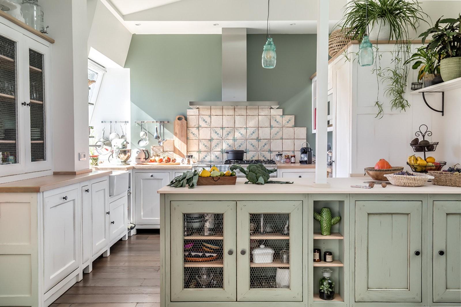 Cuisine ouverte, meublé dans son ensemble. La décoration est végétale  grâce aux couleurs verte pâle et blanc cassé. Carrelage et outils de cuisine sont disposés au mur principale ou se trouve la hôte.