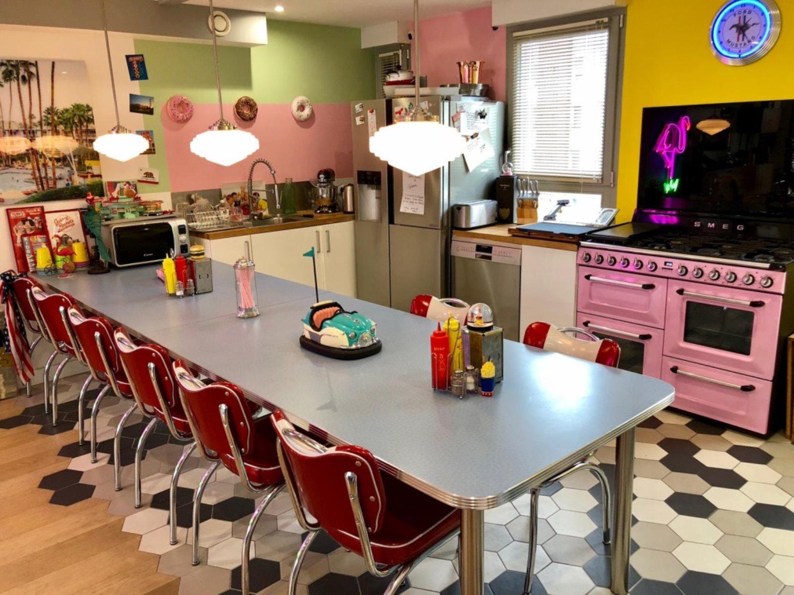 Cuisine au style vintage, coloré de rose, jaune et bordeaux. une longue table y est placé au centre. Il y a un four vintage rose pâle avec plaques de cuissons.