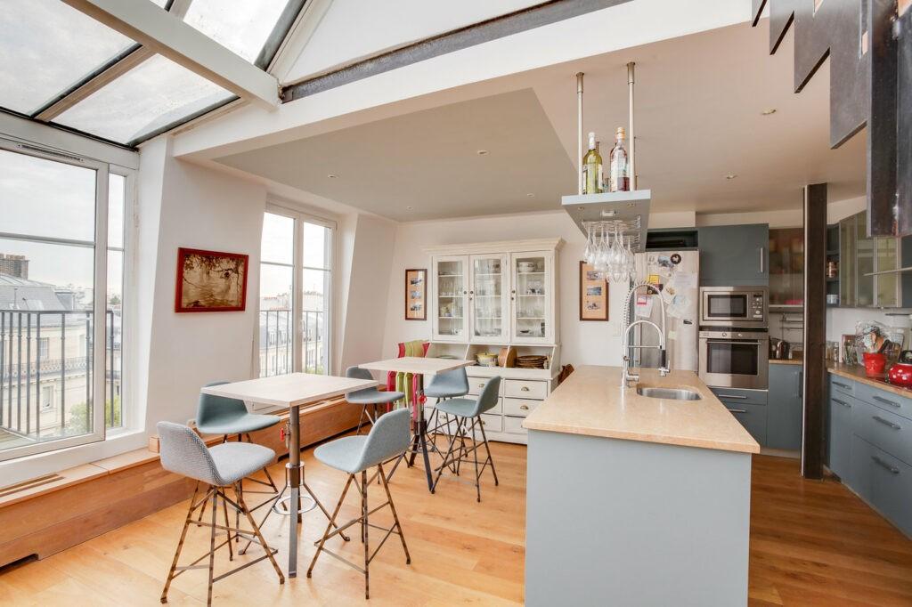 Une cuisine très lumineuse avec de larges fenêtres. Un ilot central se trouve au milieu de la cuisine avec 2 tables.