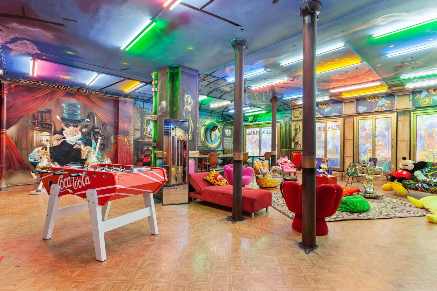 Grand loft atypique et déjanté. Cette pièce très colorée, présente toute sorte de peluches de dessin-animés, un baby-foot et des canapés originaux.