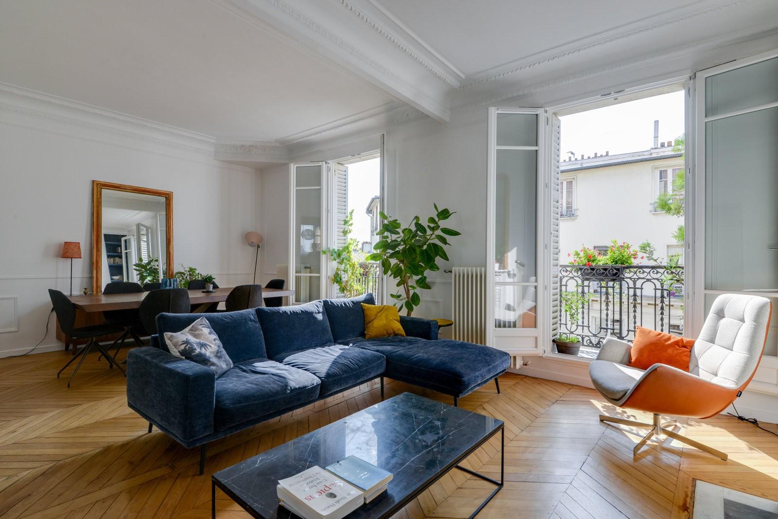 Un salon haussmannien, très chic et convivial. Appartement très lumineux, avec un canapé bleu et un fauteuil blanc et orange.