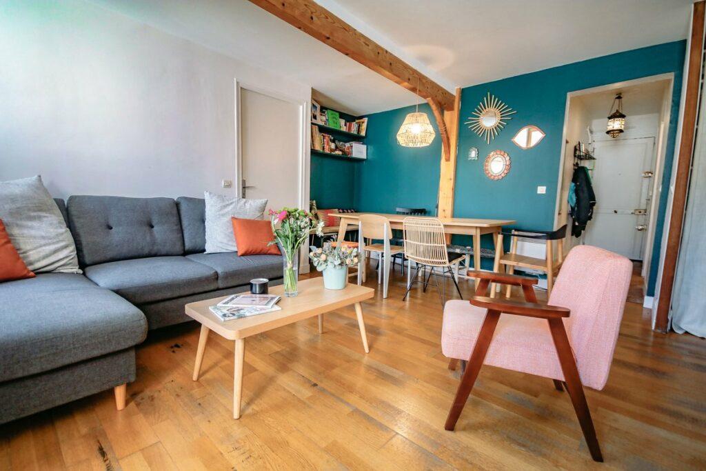Une piéce principale trés colorés avec un mur peint en bleu avec quelques décorations murales. une table a manger en bois rectangulaire se trouve sur la droite de la partie salon de l'espace ou se trouve un canapé en tissu, un fauteil rose clair et au milieu une table basse.