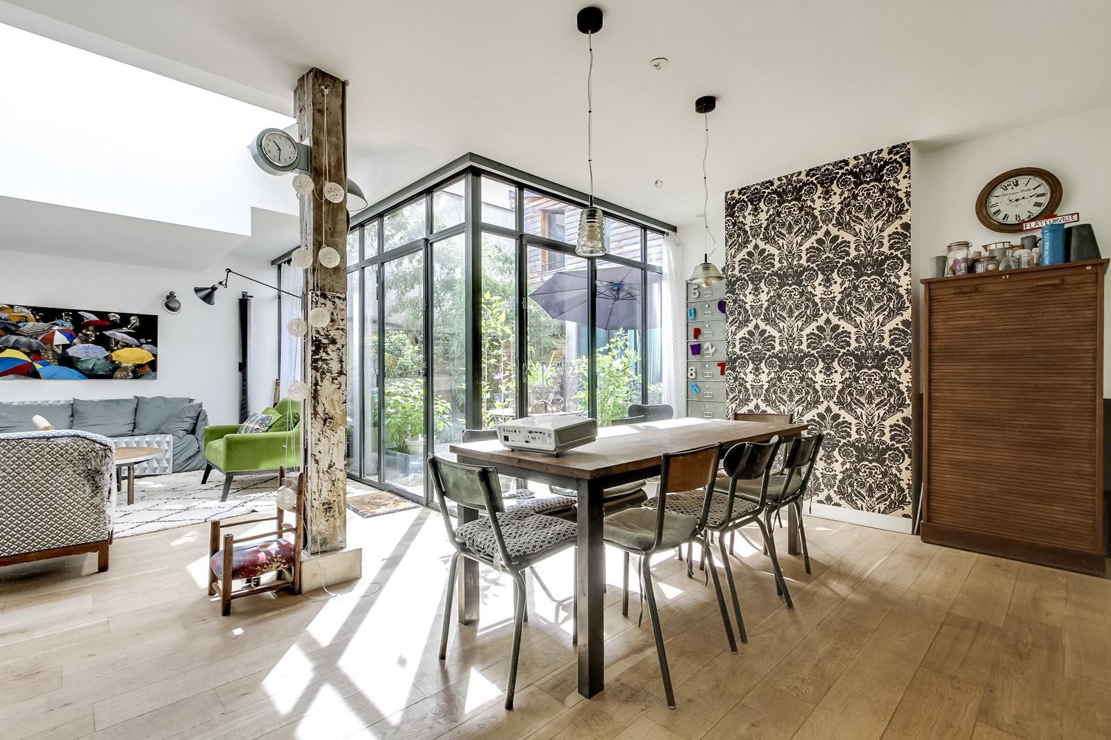Loft lumineux vintage et moderne à la fois, plancher en bois avec une verrière qui donne sur la terrasse