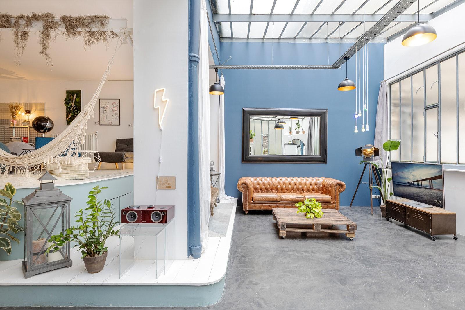 Loft industriel gris et bleu sous verrière, créatif et atypique