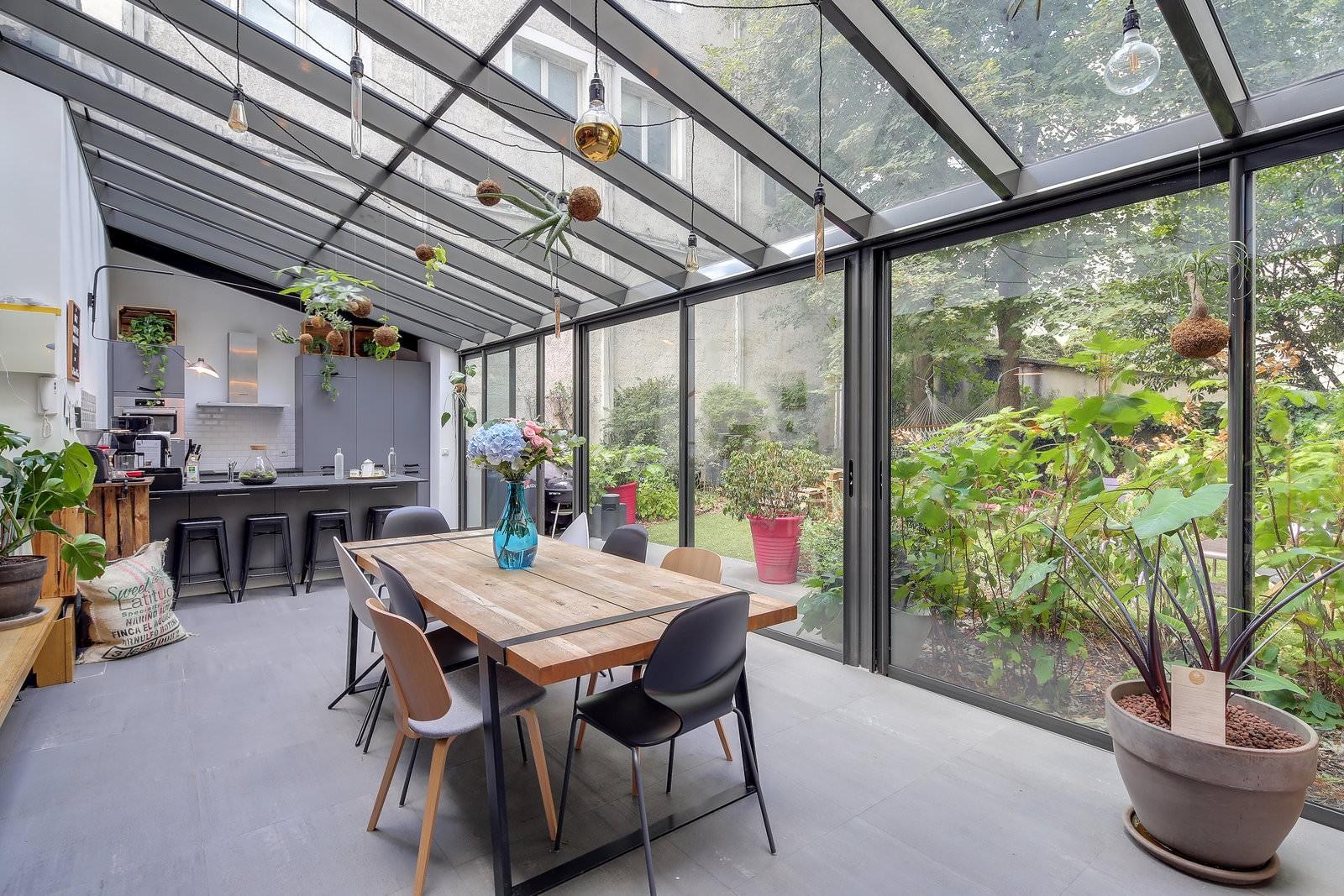 Maison moderne avec verrière, salle à manger lumineuse avec vue sur jardin