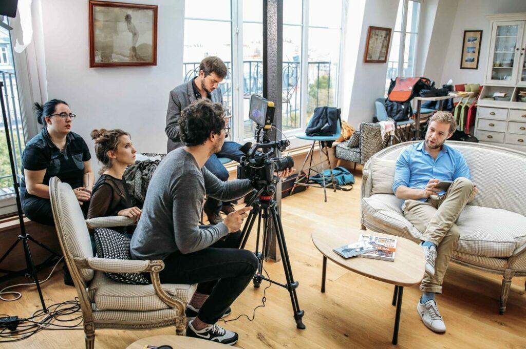 quatre personnes filment une homme assis dans un canapé