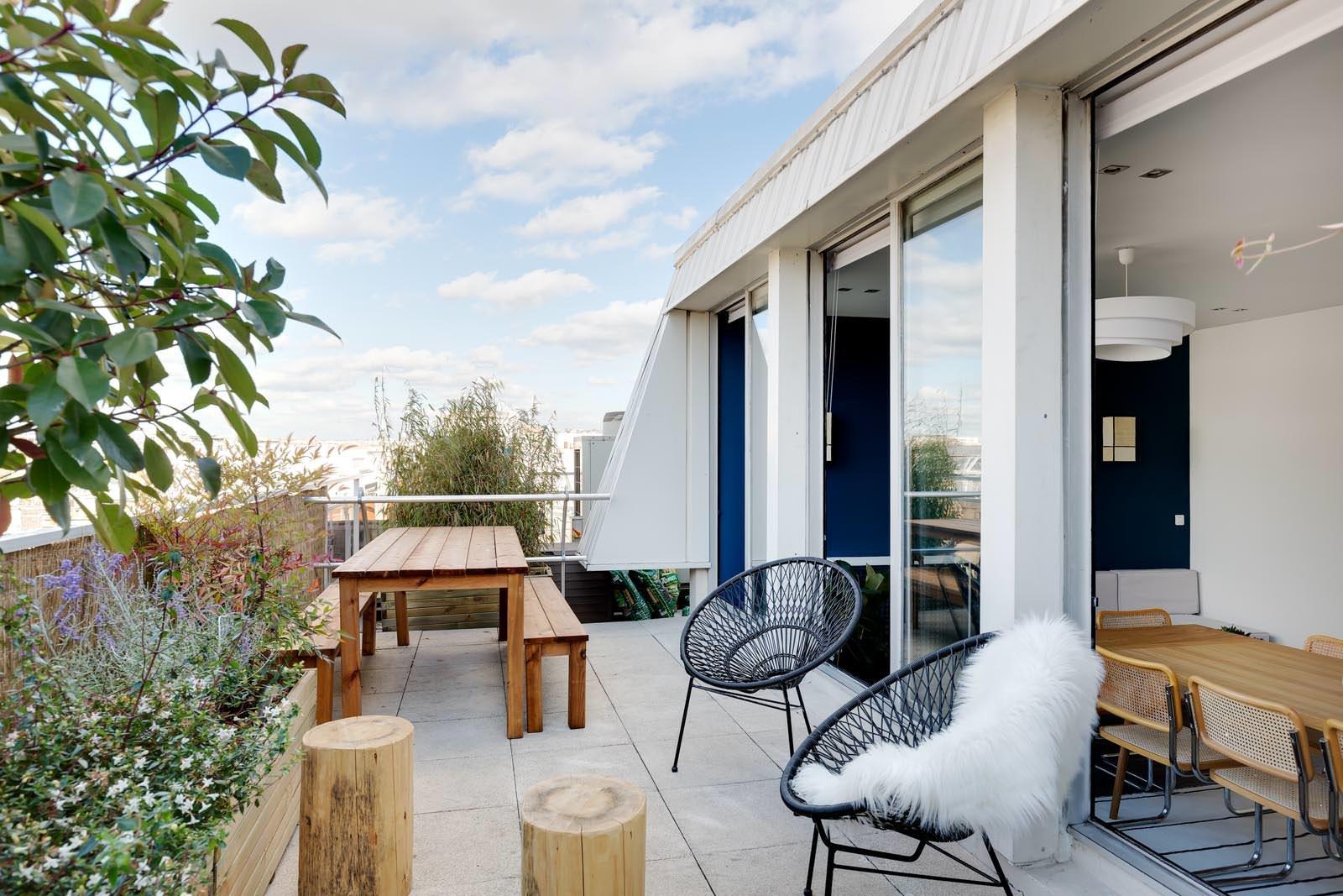 Terrasse tout en longueur donnant par des baies vitrée sur une salle de réunion intérieur. on y trouve une table longue en bois accompagné de son bac.