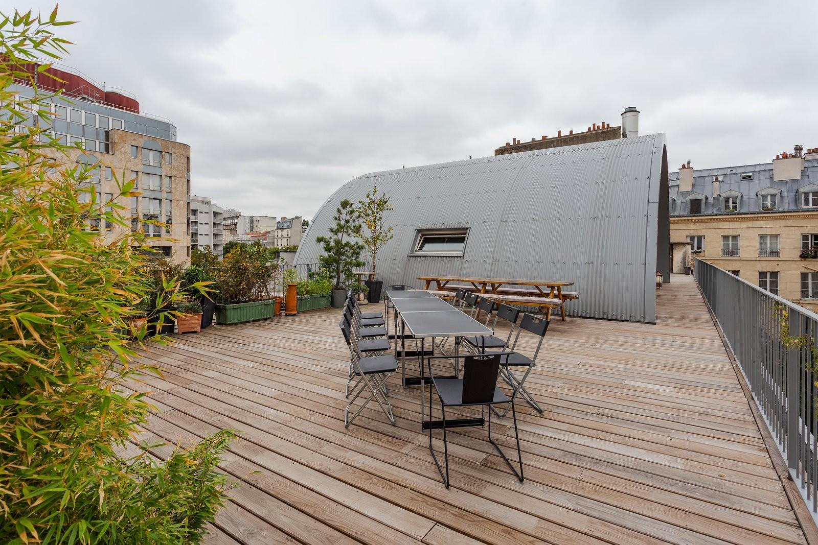 Une voute métallique est situé au milieu d'un espace extérieur avec un sol en bois. Des jardinières et buissons de bambou sont disposés à l'extrémité de la terrasse. Une longue table entourée de ses chaises est placé au milieu du rooftop.