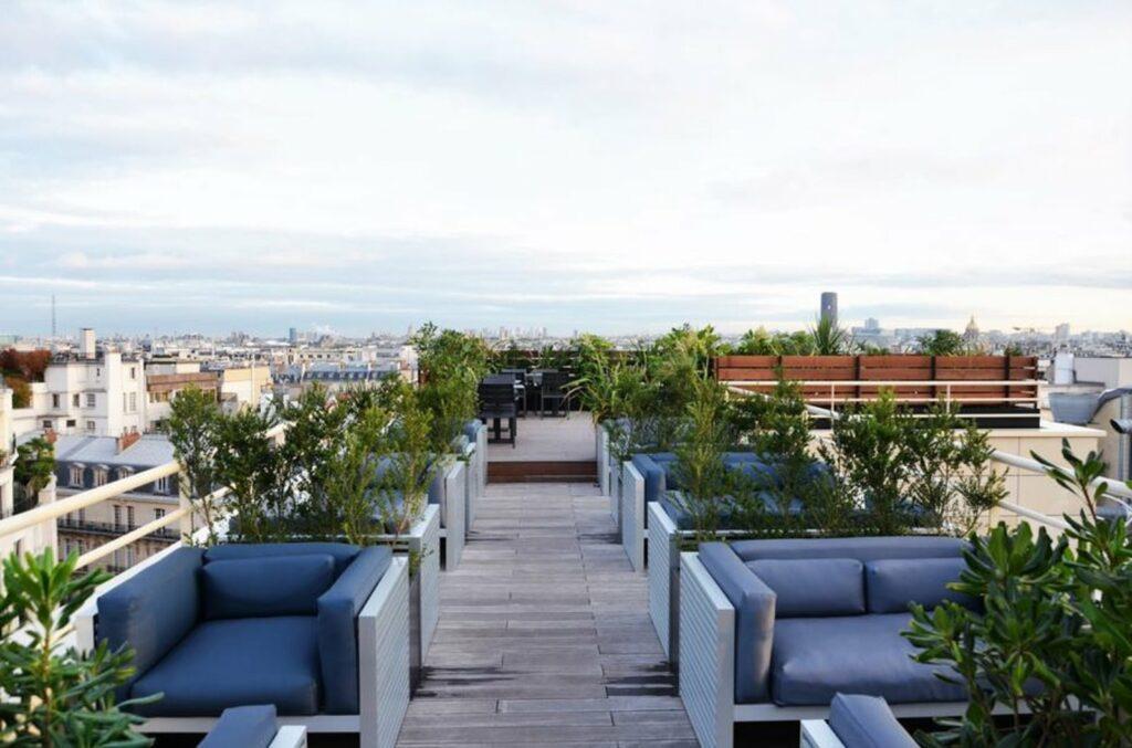 Grand rooftop avec terrasse en bois donnant vue sur la capitale
