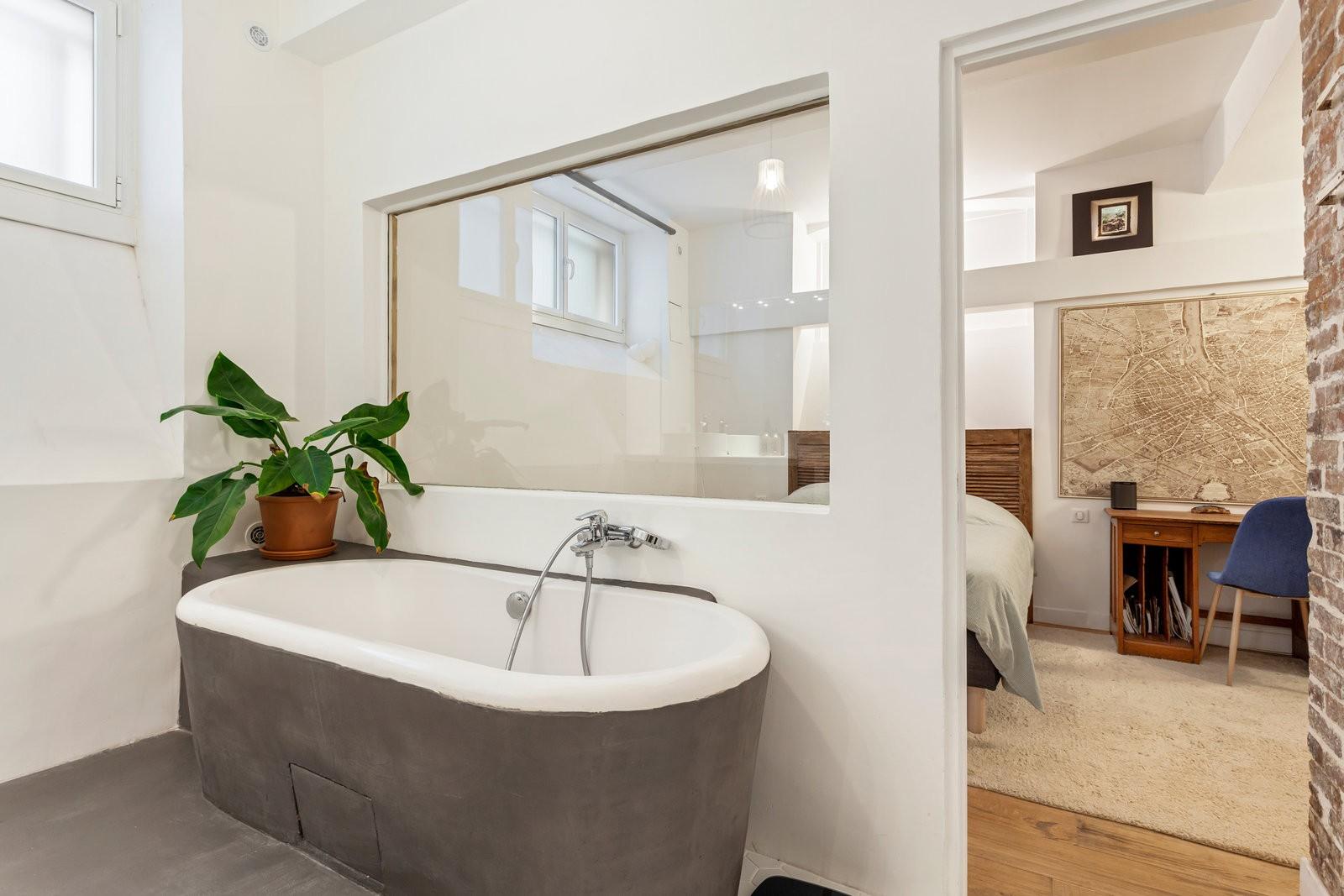 Une baignoire, couverte en extérieur de plâtre gris. Elle se situe contre un mur qui possède une vitre donnant sur la chambre.