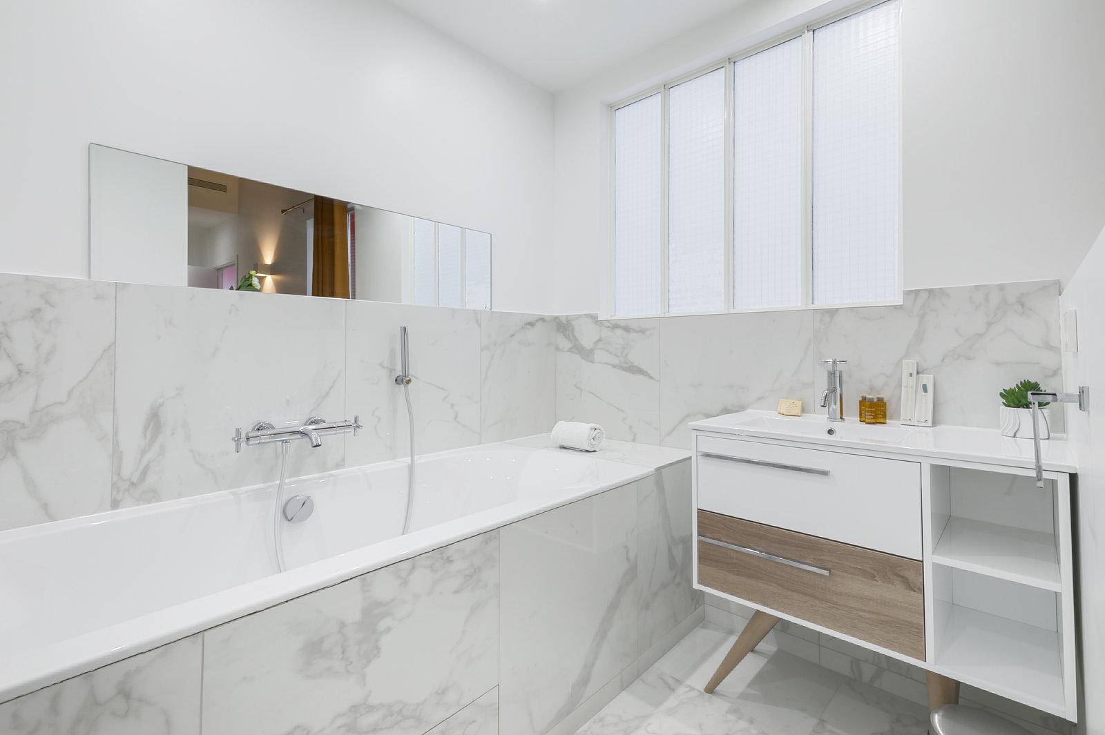 Salle de bain tout en marbre blanc. Un meuble blanc et bois avec une vasque simple est disposé à gauche de la baignoire.