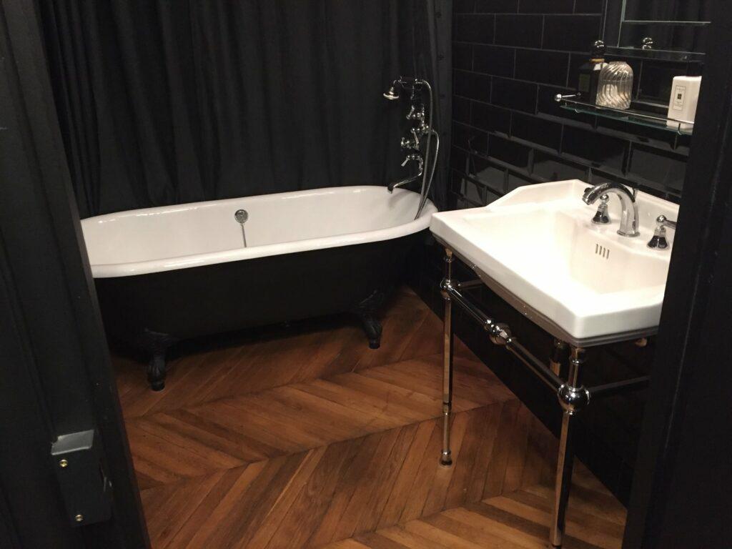Salle de bain toute noir, du mur en carrelage à la baignoire et au rideau. Une vasque simple, blanche, se trouve à gauche de la porte coulissante permettant d'accéder à l'intérieur de la pièce.