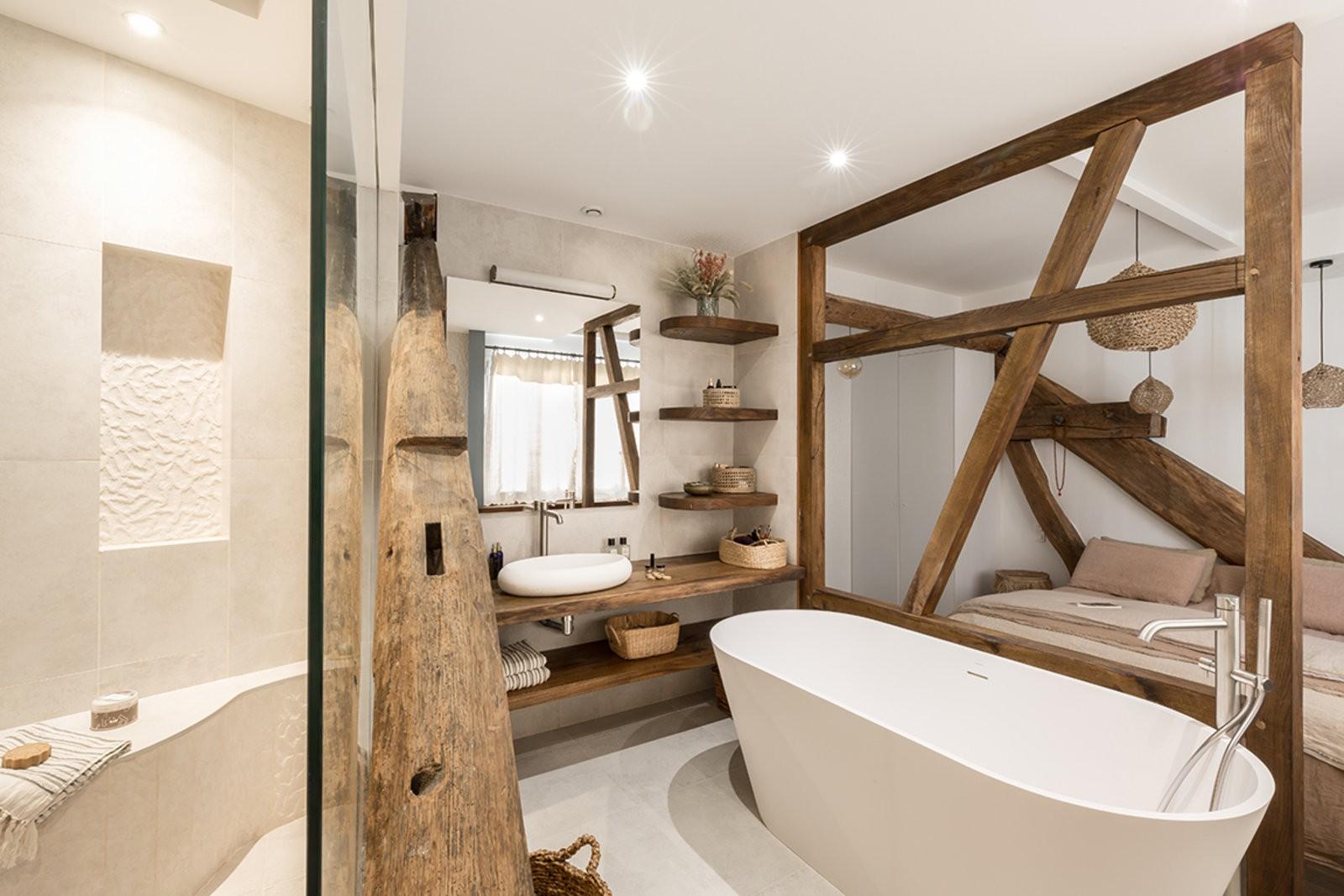 Salle de bain avec des poutres en bois disposée comme une limitation entre la chambre et la douche. Il y a une baignoire aux pieds du lit et une douche séparée d'une bais vitrée.