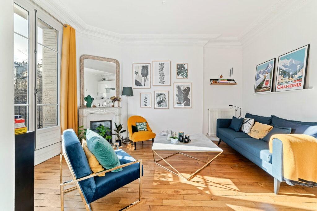 Salon design dont les couleurs dominante sont le bleu et je jaune présente sur le canapés, les assises ainsi que les rideaux et divers coussins. Au centre de la pièce se trouve une table basse design en marbre.