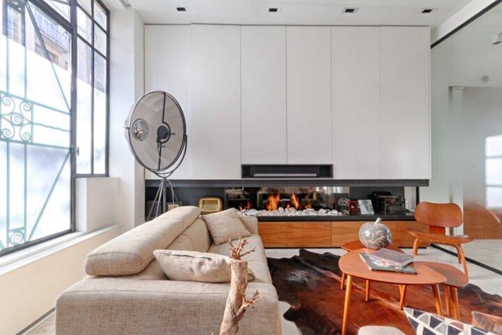 Dos à une grande fenêtre laissant entrer la lumière, il y a un canapé en tissu, couleur lin. À sa gauche il y a une cheminée design tout en longueur avec un meuble. Le tout, entour une triple tables basses en bois, sous un tapis rappelant les flammes de la cheminée.
