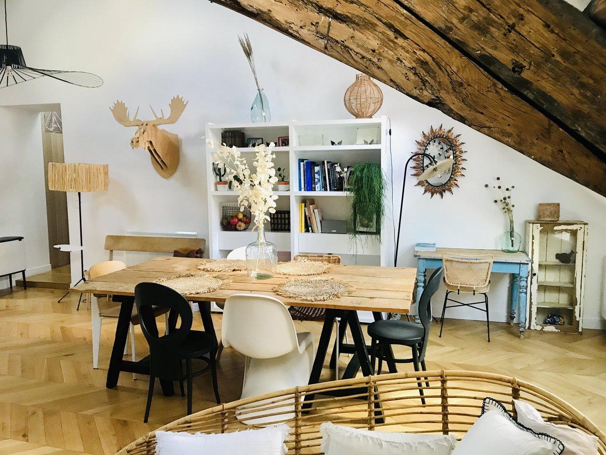 Dans une salle a manger, dans lequel il y a au centre une table rectangulaire en bois, accompagné de chaises dépareillées. Une poutre est apparente. le sol est en parquet. C'est une pièce lumineuse avec des décorations en bois sur le mur, qui entourent une étagère classe blanche remplit de livres et divers objets.