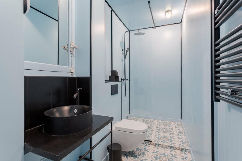 Salle de bains tout en longueur et en couleur, bleu ciel et noir. Avec un toilette et une vasque simple (noir) avec un miroir.