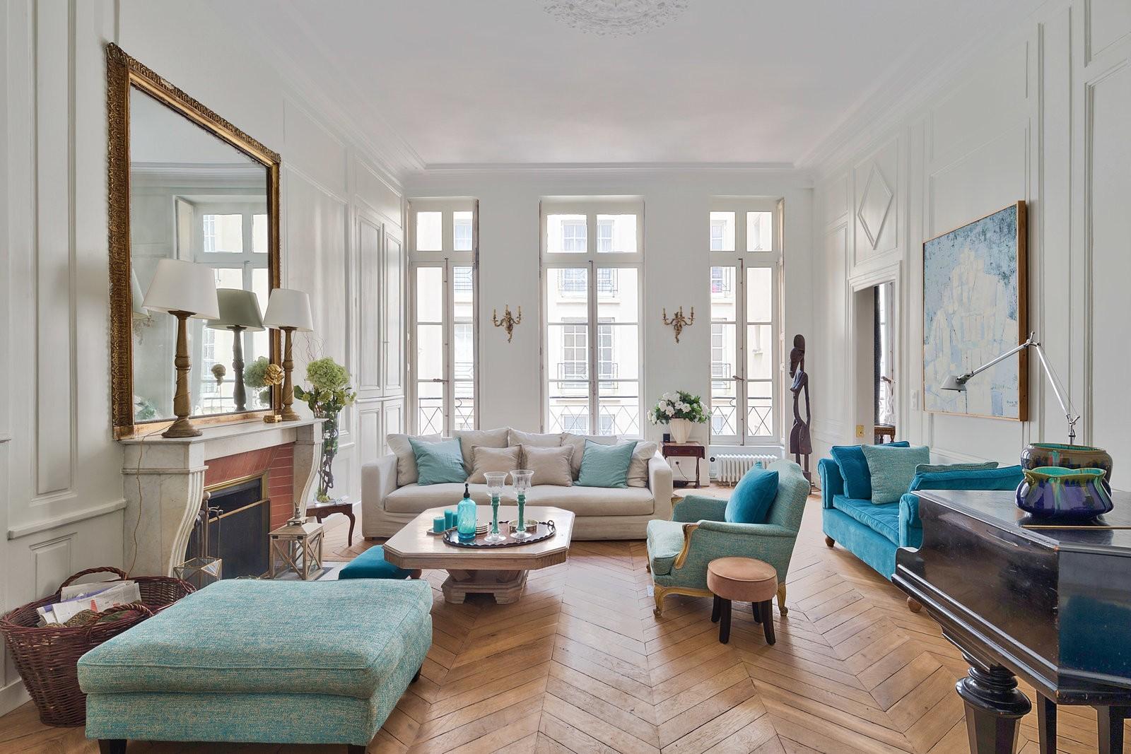 Grand salon rectangulaire, peint de blanc avec du parquet au sol. il y a un grand miroir orné de dorure placé au dessus de la cheminée. les canapés sont bleue ciel placé autour d'une table basse.