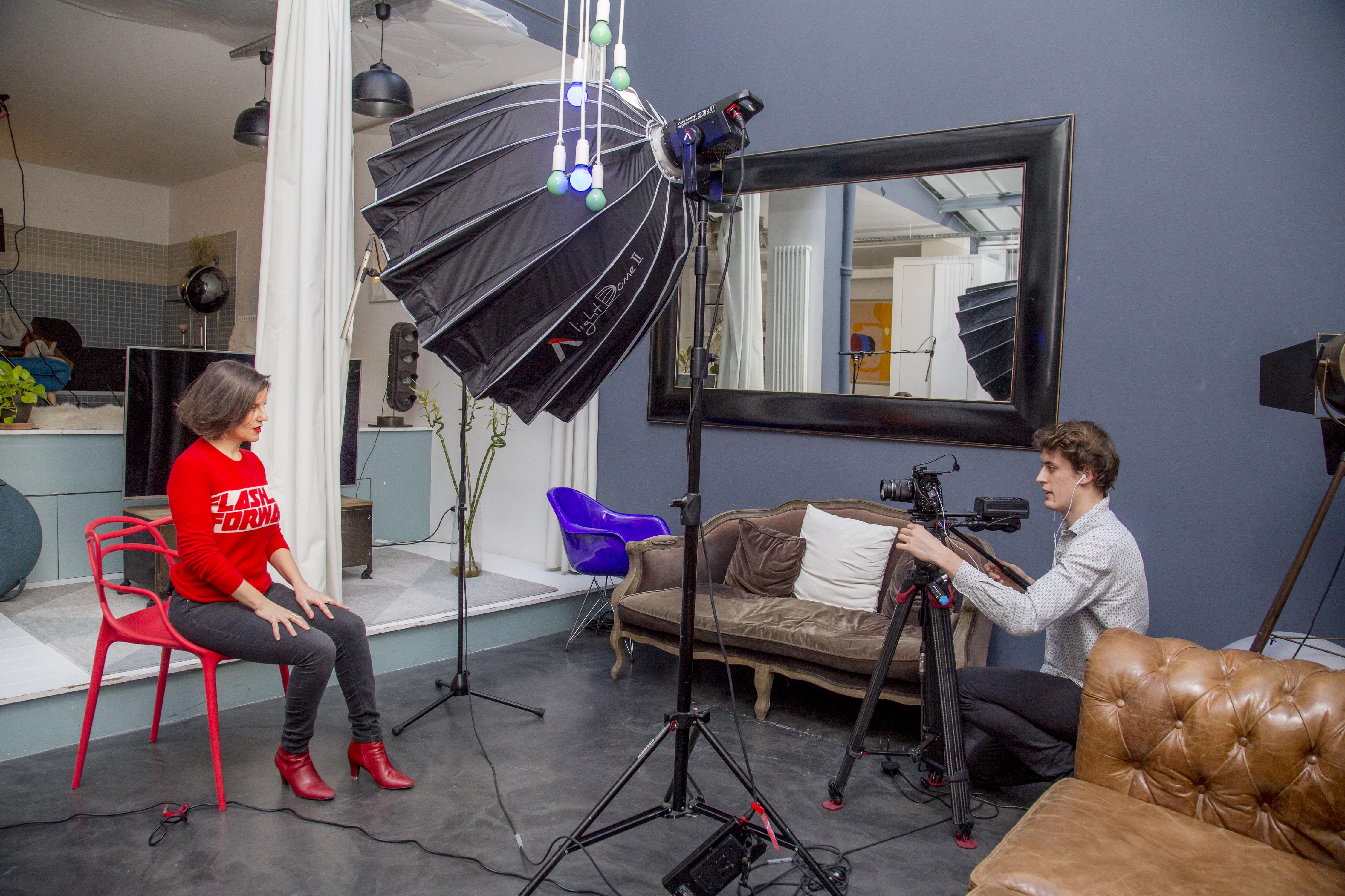 Un homme filme une femme assise sur une chaise