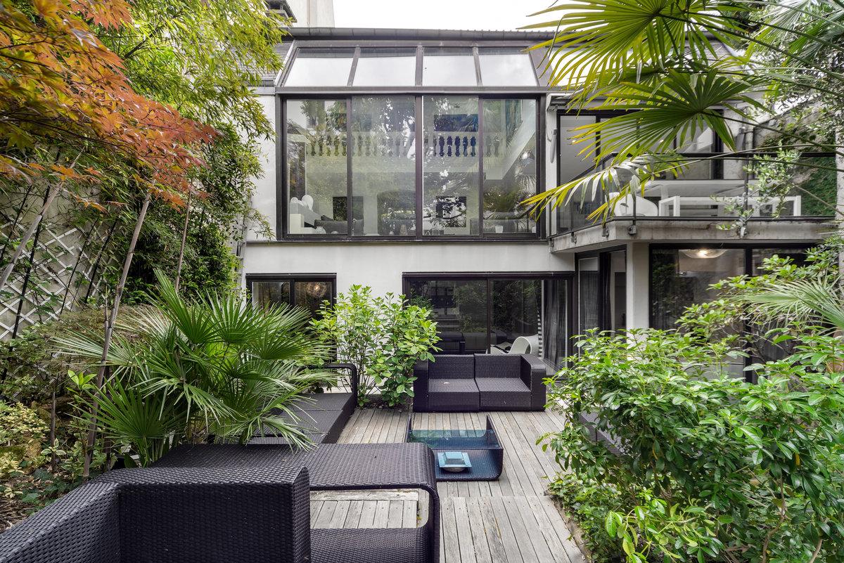 Grande villa moderne noire et blanche avec un jardin arboré pour accueillir vos réunions, événements ou productions