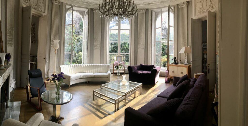 Appartement très luxueux, la pièce est en arrondit avec des moulures aux plafonds et sur les murs. Un grand lustre surplombe la pièce. des canapés sont disposés en cercle et au milieu se troue une table basse en verre.